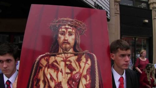"""http://www.tfpstudentaction.org/ -- """"A dog may bark in his master's defense, and am I to stand by silent when God's holy name is blasphemed? -- Saint Jerome  To defend Our Lord's honor, TFP Student Action volunteers joined dozens of America Needs Fatima members and New York City area Catholics on Sunday, September 1, to protest the blasphemous movie called Paradise: Faith.   The immoral picture, produced by the Austrian film maker Ulrich Seidl, not only reviles the Catholic Faith, but depicts the crucifix of Our Lord Jesus Christ in a lewd manner.  Why is sacred Person of Our Lord repeatedly singled out for such vile attacks?  Movie-goers purchasing tickets at the Village East Cinema in Lower Manhattan met an unusual sight that day: a throng of faithful, both young and old, peacefully praying on the sidewalk in front of the cinema.  """"Reparation, reparation, reparation!"""" was chanted loudly and in unison between the recitation of each rosary.  And hymns to Our Lady were sung.  A similar protest was also organized by the TFP in Los Angeles, California, earlier in the week.   Let us continue to work, fight and pray to banish blasphemy from our land and culture.  ------ Connect with us:  http://www.facebook.com/TFPStudentAction https://twitter.com/tfpsa http://www.tfpstudentaction.org/"""